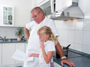 Father and daughter looking at a recipe