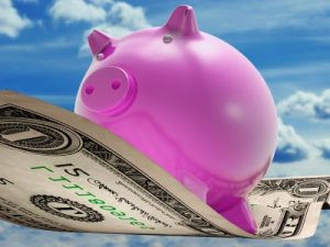 pink pig bank flying on a dollar bill